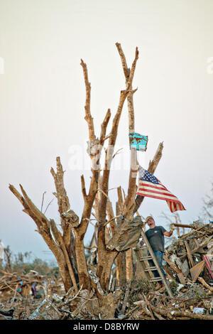 Ein Bewohner Hände eine Fahne von einem zerstörten Baum, wie sie durch den Trümmern ihrer Häuser im Anschluss an - Stockfoto