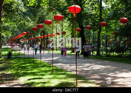 Menschen schlendern Sie entlang einem Pfad gesäumt mit Lampions in Łazienki Park Łazienkowski, der größten Grünanlage - Stockfoto