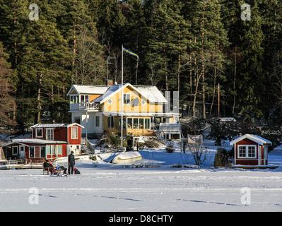 Familie mit Picknick auf dem Eis bedeckt See im Winter, Lidingö Insel Stockholm, Schweden - Stockfoto