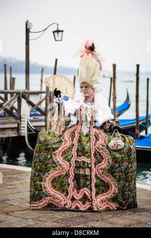 Eine Frau trägt einen spektakulären Karnevalskleid posiert auf der Venedig-Uferpromenade. Italien. - Stockfoto