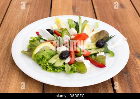 Griechischer Salat mit Feta, Tomaten, Gurken, Paprika und schwarzen Oliven auf einem Holztisch. - Stockfoto