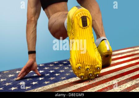 Sprinter mit Spikes ist in Grundstellung auf trashigen US-Flagge - Stockfoto