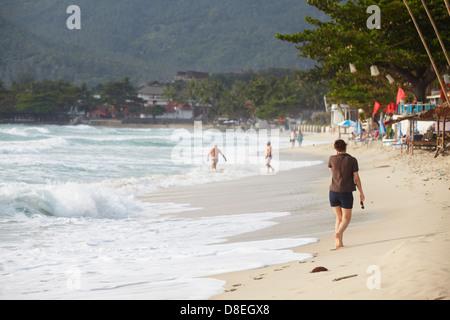 Frau zu Fuß entlang Chaweng Beach, Ko Samui, Thailand - Stockfoto