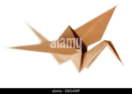 Origami Kranich Vogel aus Braun Recycling-Papier hergestellt. Isoliert auf weißem Hintergrund - Stockfoto