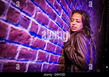 Hübsche junge Frau gegen eine Mauer Angst in der Nacht. - Stockfoto