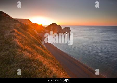 Der Morgendämmerung bricht über Durdle Door an der Küste von Dorset.