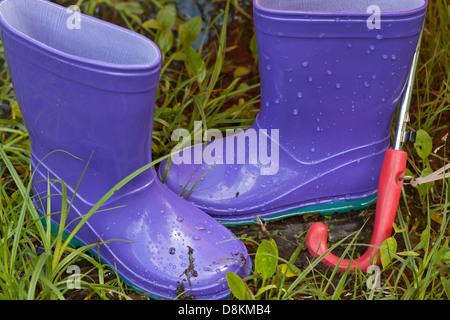 Gummistiefel in regnerischen Frühlingstag auf dem grünen Rasen - Stockfoto