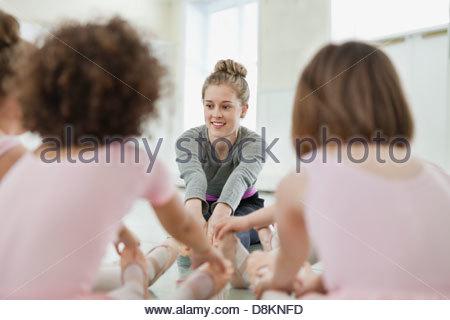 Weibliche Ballett Lehrer unterrichten von Kindern erstreckt sich im Ballettstudio - Stockfoto