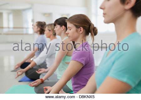 Gruppe von Menschen praktizieren Lotussitz im Yoga-studio - Stockfoto