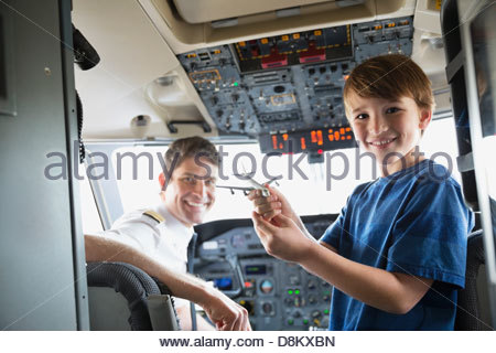 Porträt eines jungen halten Spielflugzeug mit männlichen Piloten im Flugzeug-cockpit - Stockfoto