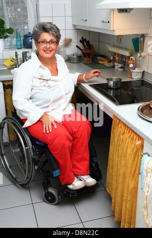 Frau in einem Rollstuhl in der Küche - Stockfoto