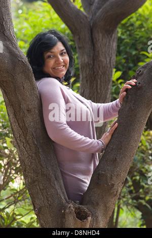 Rumänische Latino-Frau mittleren Alters posieren von Baum - Stockfoto