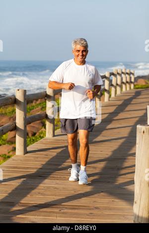 aktive glücklich Mann mittleren Alters Joggen am Strand am Morgen - Stockfoto