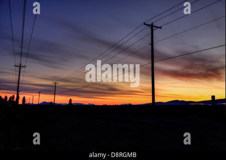 Stromleitungen und Stöcke sind gegen den Sonnenaufgang Himmel abhebt. - Stockfoto