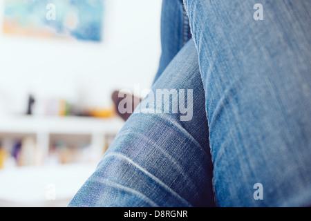 Frau Beine gekreuzt tragen Blue Jeans entspannend auf Trainer in einem weißen Raum - Stockfoto