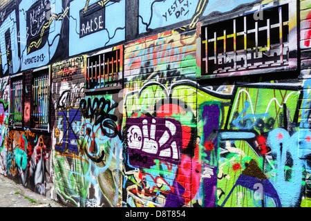 Bunte Graffiti in Gasse an der Wand des Gebäudes in der Stadt - Stockfoto