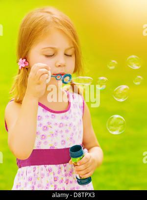Closeup Portrait von niedlichen Babymädchen bläst Seifenblasen im freien Spiel auf Frühlingsgarten, sonnigen Tag, - Stockfoto