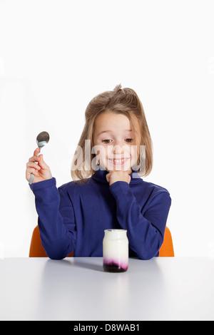 Pürieren Sie glückliches Mädchen essen ein Naturjoghurt mit blackberry - Stockfoto
