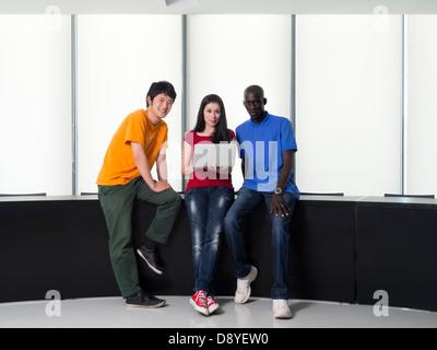 Schwarzer Mann, asiatischen Mann und kaukasischen Frau versammelten sich um einen Laptop-computer - Stockfoto