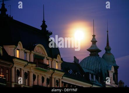 Der Mond über Häuser mit Türmen und Zinnen. - Stockfoto