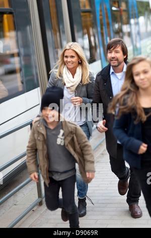 Familie mit zwei Kindern auf Straßenbahn einsteigen Stockfoto