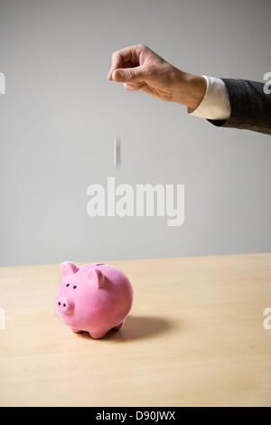 Ein Mann, ein Sparschwein Geld einlegen. - Stockfoto