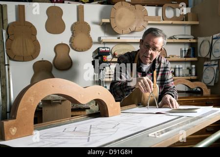 Gitarrenbauer arbeitet an Plänen für eine akustische Gitarre in Werkstatt - Stockfoto