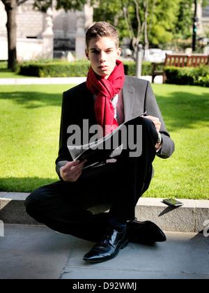 Ein junger Geschäftsmann hält eine Zeitung sitzend in einem park - Stockfoto