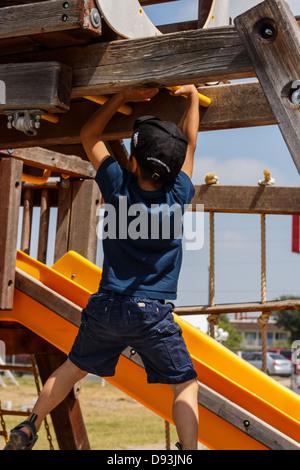 Kleiner Junge am Klettergerüst auf dem Spielplatz spielen - Stockfoto