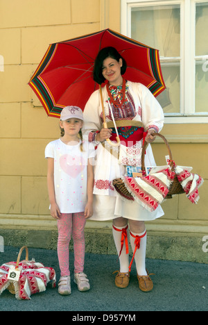 Frau auf kroatischen nationalen Kostüm posiert mit touristischen Maedchen, Straßenecke in Zagreb, Kroatien, Europa - Stockfoto