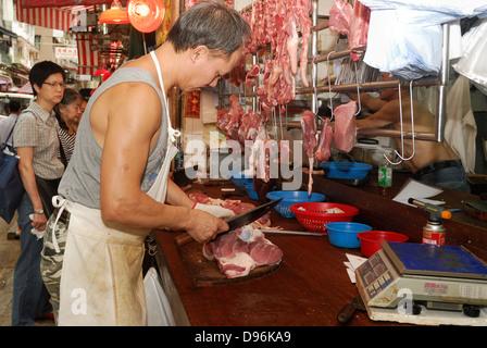Metzger Schneiden von Fleisch in Outdoor-Straßenmarkt, Hong Kong China. - Stockfoto