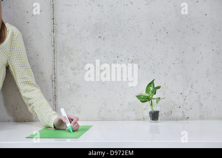 Deutschland, Nordrhein-Westfalen, Köln, Geschäftsfrau, die auf dem Papier zu schreiben - Stockfoto