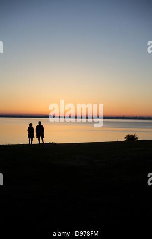 Ein älteres Ehepaar Sonnenuntergang über einer noch Bucht in Irland Dublin City gesetzt. - Stockfoto