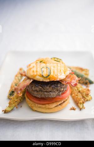 Burger Speck Tomaten Senf Jalapeño Käse Brötchen und Zucchini fries - Stockfoto