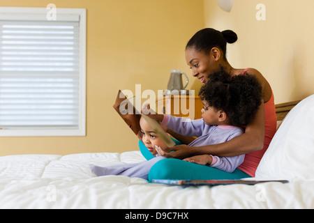 Mutter und Tochter im Bett lesen - Stockfoto