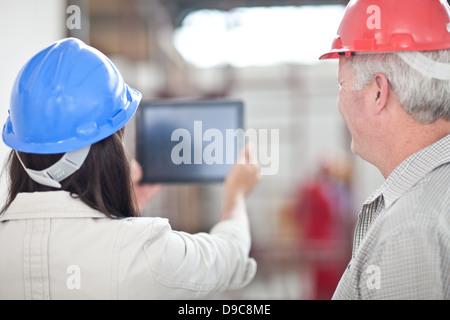Rückansicht des Kollegen Blick auf digital-Tablette auf Baustelle - Stockfoto