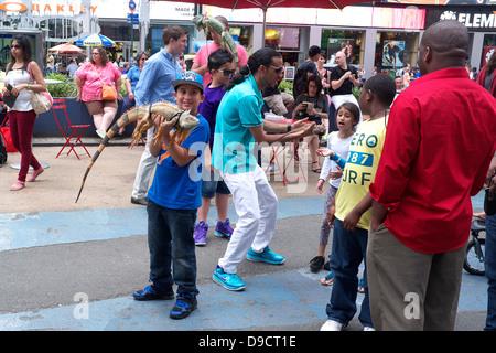 Junge hält einen großen Leguan in Times Square in New York City und ein kleines Mädchen blickt auf angewidert - Stockfoto