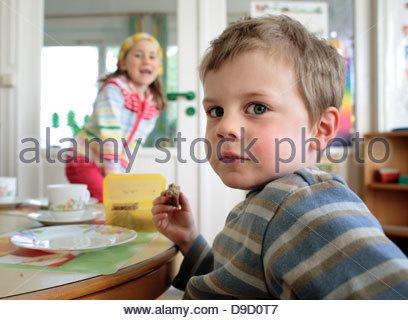 Schuljunge zu Mittag mit einer Schülerin im Hintergrund - Stockfoto