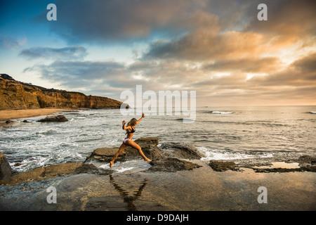 Junge Frau im Bikini am Strand von Felsen springen. - Stockfoto