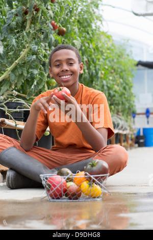 Junge sitzt cross legged Betrieb reife Tomate - Stockfoto