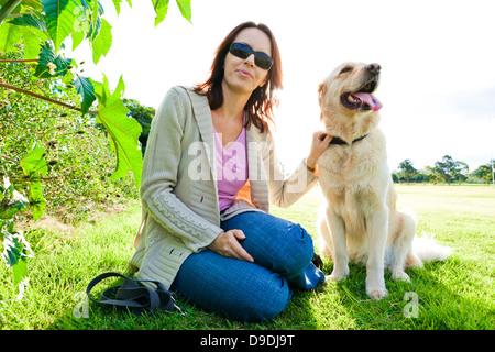 Junge Frau und golden Retriever sitzend in den Rasen | - Stockfoto