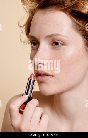 Junge Frau Auftragen von Lippenstift, Nahaufnahme - Stockfoto