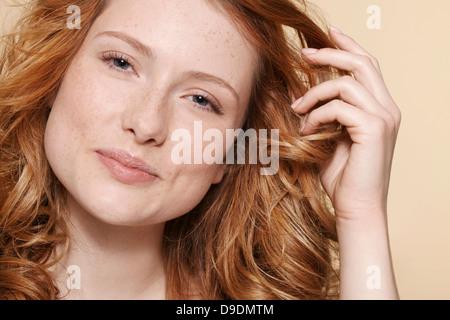 Studioaufnahme der jungen Frau mit lockigen roten Haaren, hand im Haar - Stockfoto