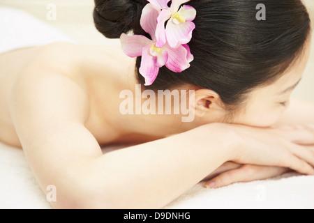 Frau mit rosa Blume im Haar - Stockfoto