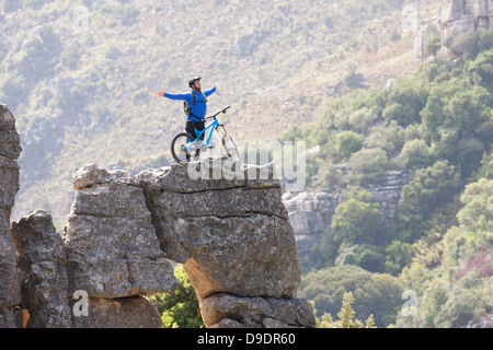 Junger Mann mit Mountainbike und Arme ausgestreckt auf Felsen - Stockfoto
