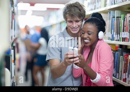 Schüler hören mp3-Player in Bibliothek - Stockfoto