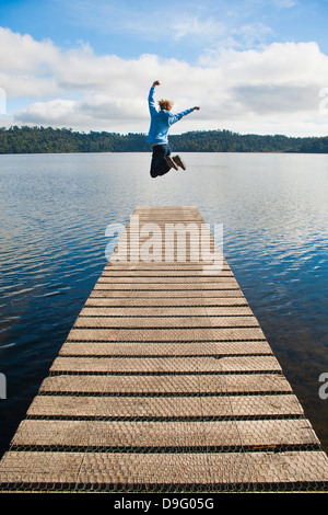 Frau, springen auf einem Steg am See zeichnet, West Coast, Südinsel, Neuseeland - Stockfoto