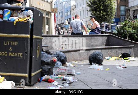 Brighton UK 19. Juni 2013 - ein paar genießen Sie ein Picknick neben nicht abgeholte Müllberge im Stadtzentrum von - Stockfoto