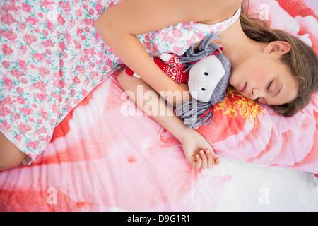 Mädchen schläft auf dem Bett mit einer Stoffpuppe - Stockfoto