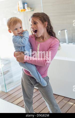 Mädchen tragen ihren Bruder und suchen in einem Badezimmer überrascht - Stockfoto